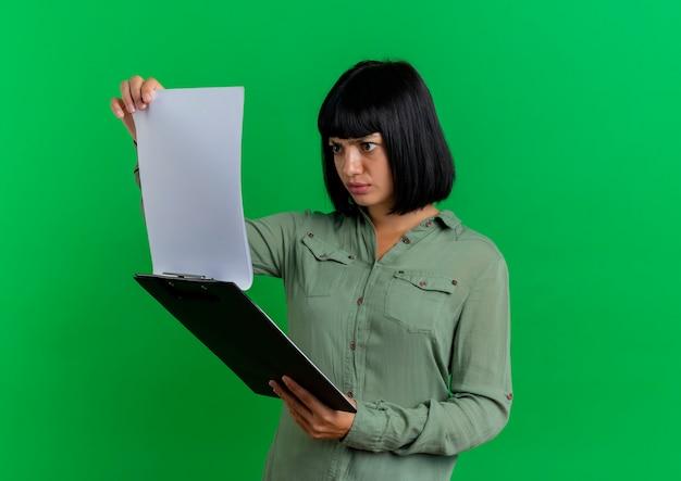 Ernstige jonge brunette blanke vrouw houdt en kijkt naar klembord geïsoleerd op groene achtergrond met kopie ruimte