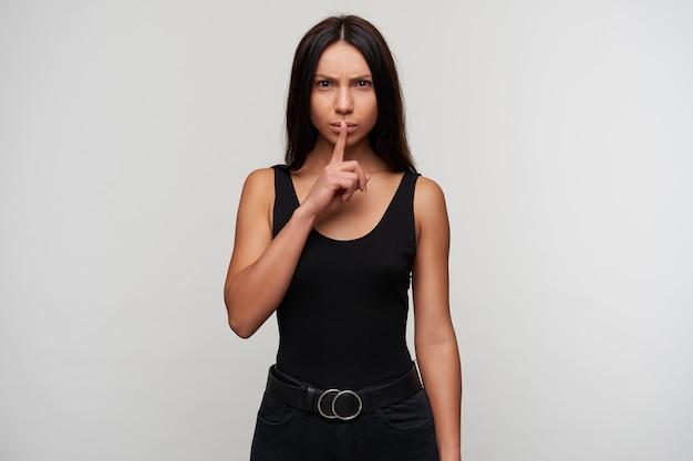Ernstige jonge brunette dame met bruine ogen in casual zwarte kleding met wijsvinger op haar lippen en fronsende wenkbrauwen, vraagt om stilte te houden, staande tegen wit
