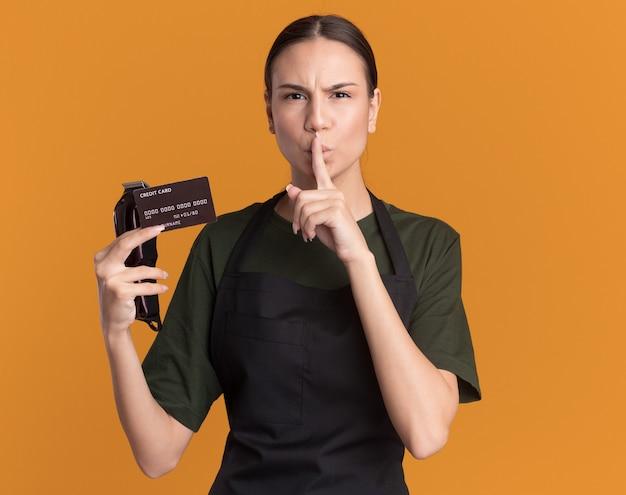 Ernstige jonge brunette kapper meisje in uniform met tondeuses en creditcard doen stilte gebaar geïsoleerd op oranje muur met kopie ruimte