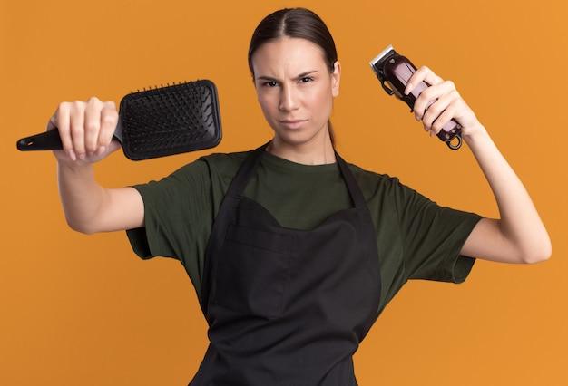 Ernstige jonge brunette kappersmeisje in uniform houdt tondeuses en kam vast