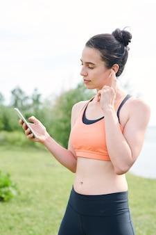 Ernstige jonge brunette vrouw draadloze koptelefoon aanpassen tijdens het kiezen van muziek voor yoga training buitenshuis