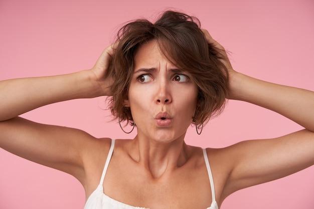 Ernstige jonge brunette vrouw met kort haar hand in hand op haar hoofd en opzij kijken met verward gezicht, lippen vouwen en fronsende wenkbrauwen terwijl poseren