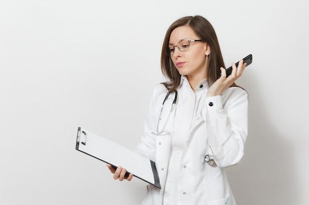 Ernstige jonge dokter vrouw met stethoscoop, bril geïsoleerd op een witte achtergrond. vrouwelijke arts in medische toga praat op mobiele telefoon, houd gezondheidskaart op notitieblokmap. gezondheidszorg personeel concept.