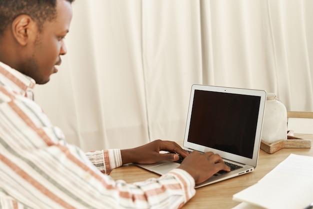 Ernstige jonge donkere man werken vanuit huis keyboarding op draagbare computer met lege zwarte display