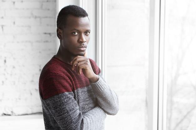 Ernstige jonge donkere ontwerper in gezellige warme trui met doordachte blik