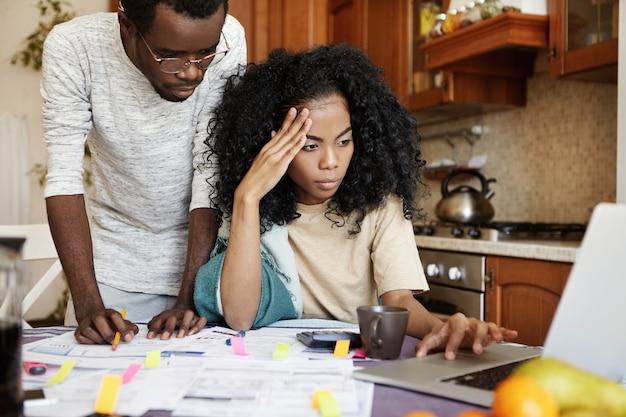 Ernstige jonge donkere vrouw met afro kapsel zit open laptop