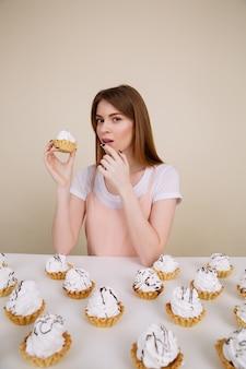 Ernstige jonge en dame die terwijl het houden van cupcake zitten stellen