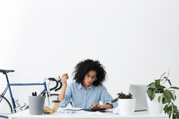Ernstige jonge gemengde ras vrouwelijke accountant die aan financieel verslag werkt