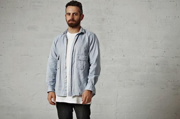 Ernstige jonge hipster die een licht denim losgeknoopt overhemd over een leeg wit t-shirt en een zwarte spijkerbroek draagt