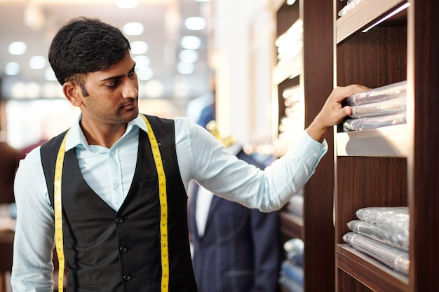 Ernstige jonge indiase kleermaker kijkt naar verpakte afgewerkte kledingstukken, bestellingen in de schappen