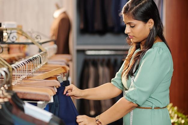 Ernstige jonge indiase vrouw die broek controleert op hanger in warenhuis