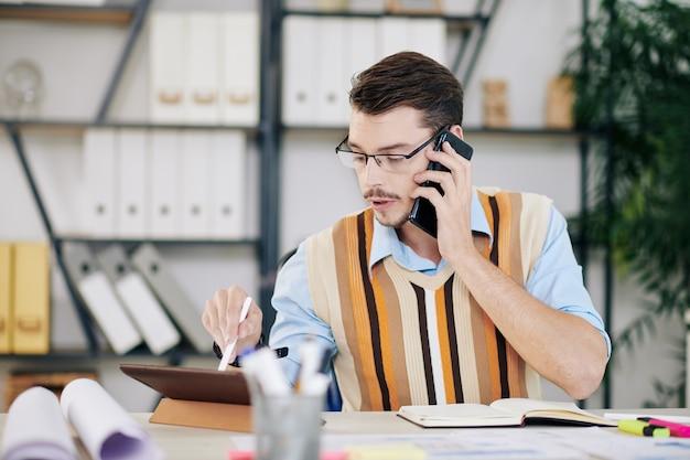 Ernstige jonge ingenieur met een bril die documenten of e-mails controleert op het scherm van de tabletcomputer tijdens een telefoongesprek met een collega of klant