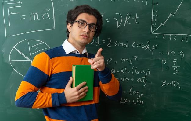 Ernstige jonge kaukasische meetkundeleraar met een bril die voor het bord staat in de klas met een boek