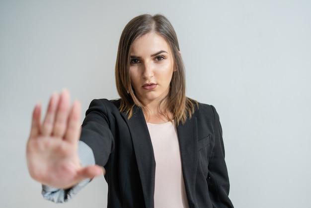 Ernstige jonge kaukasische zakenvrouw weergegeven: stop gebaar