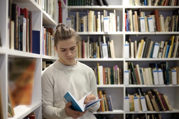 Ernstige jonge kerel die trui draagt die zich in boekhandel bevindt, uittreksel uit leerboek in zijn handen leest, leunend op witte planken vol met boeken