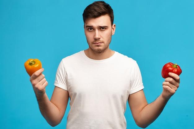 Ernstige jonge kerel met borstelharen die oranje en rode paprika vasthoudt met besluiteloze gezichtsuitdrukking, twijfels en vermoedens heeft, wil geen pesticidengroenten eten