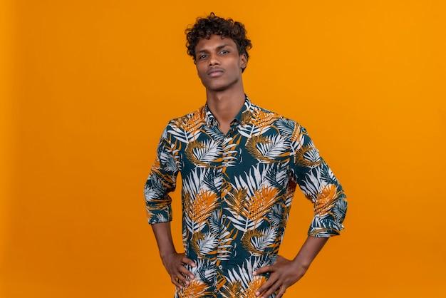Ernstige jonge knappe donkere man met krullend haar in bladeren bedrukt shirt camera kijken op een oranje achtergrond
