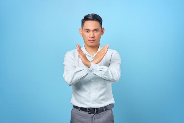 Ernstige jonge knappe zakenman gekruiste hand en weigering gebaar tonen op blauwe achtergrond