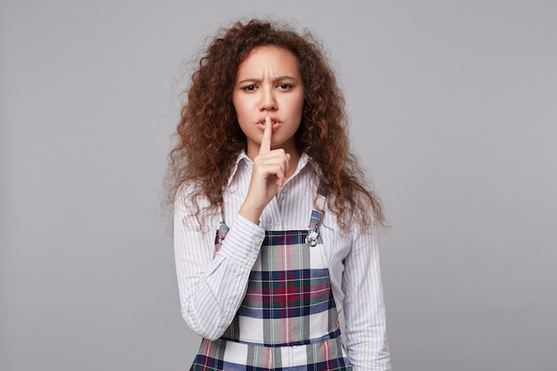 Ernstige jonge langharige brunette met krullend haar fronste wenkbrauwen en houdt de wijsvinger op haar lippen terwijl ze vraagt om te zwijgen, geïsoleerd op grijs