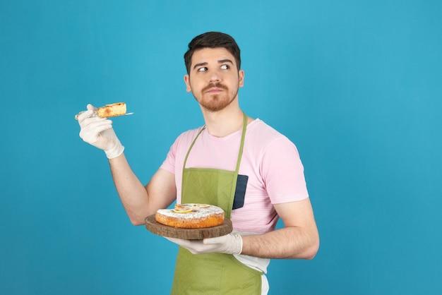 Ernstige jonge man die cakeplak omhoog houdt en wegkijkt.