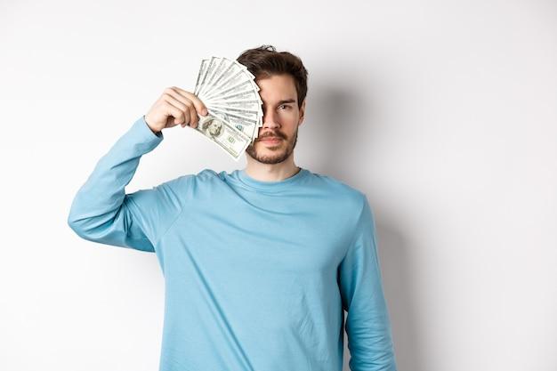 Ernstige jonge man die de helft van het gezicht bedekt met geld, naar de camera kijkt, in een blauwe sweater op een witte achtergrond staat.