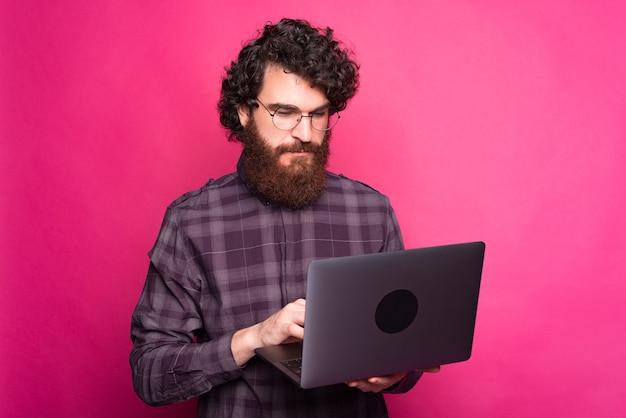 Ernstige jonge man die een computer vasthoudt en ernaar kijkt