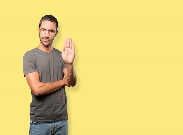 Ernstige jonge man die een stop-gebaar maakt met zijn handpalm