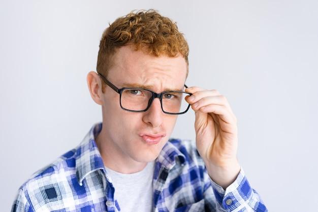 Ernstige jonge man fronsen en glazen aan te passen