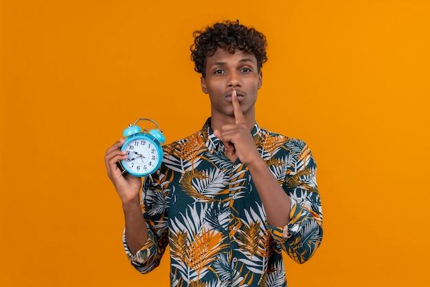 Ernstige jonge man in shirt shh gebaar met wijsvinger in de buurt van mond tonen terwijl wekker op een oranje achtergrond