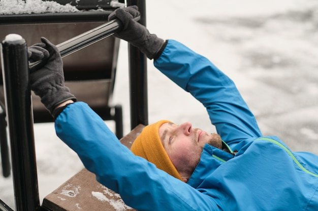 Ernstige jonge man liggend op de oefenbank buiten en het houden van horizontale balk tijdens het doen van crunches tijdens training in de winter