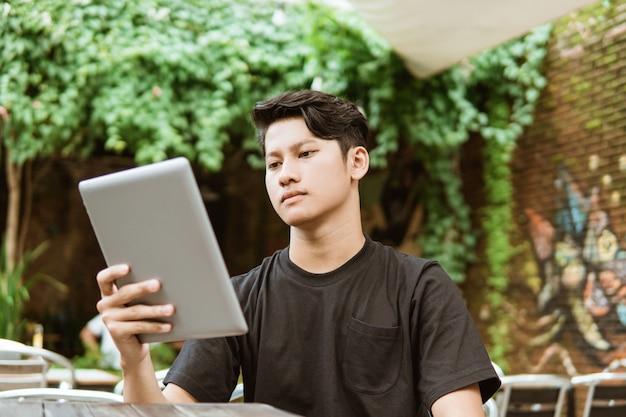 Ernstige jonge man met behulp van een tablet-pc