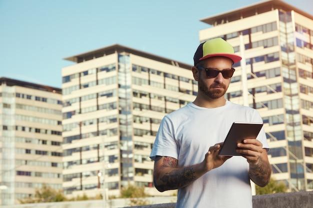 Ernstige jonge man met een wit effen t-shirt en een rode, gele en zwarte vrachtwagenchauffeurhoed die naar zijn tablet kijkt tegen stadsgebouwen en lucht