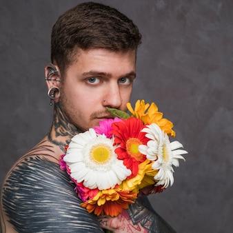 Ernstige jonge man met gepiercete oren en neus met gerbera bloem in de voorkant van zijn mond
