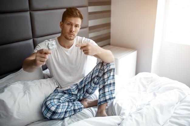 Ernstige jonge man op bed in de vroege ochtend. hij houdt condoom in de hand en wijst erop. volwassen en sexy.