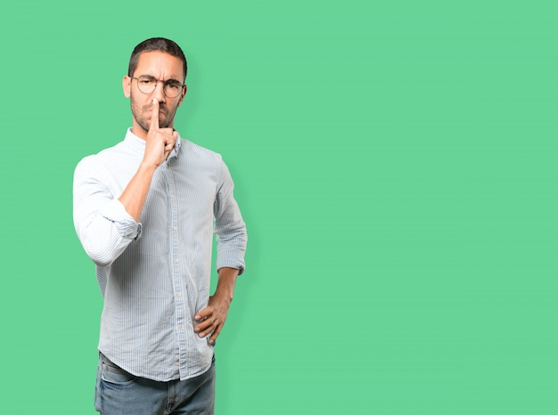 Ernstige jonge man vraagt om stilte gebaren met zijn vinger