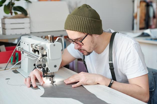 Ernstige jonge mannelijke leerbewerker die over elektrische naaimachine buigt terwijl hij stuk leer onder de naald houdt tijdens het werk