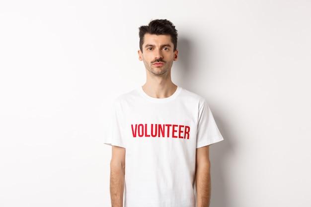 Ernstige jonge mannelijke vrijwilliger in wit t-shirt kijkend naar camera, klaar om te helpen