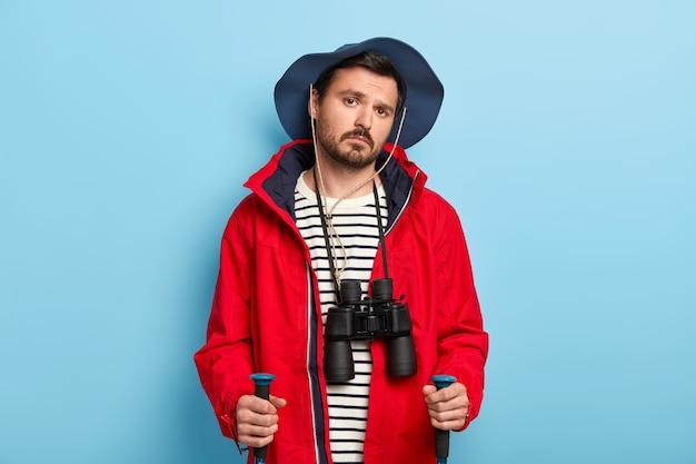 Ernstige jonge mannelijke wandelaar heeft reis in het bos, gebruikt trekkingstokken, geniet van reislevensstijl, draagt een verrekijker op de nek, draagt een casual hoed en een rode jas, geïsoleerd op blauwe muur