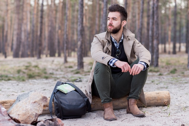 Ernstige jonge mannelijke wandelaar met zijn rugzak zittend op logboek op strand