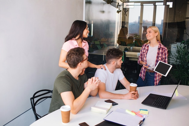Ernstige jonge mannen zitten aan tafel en kijken naar laptopscherm. achter hen staan brunette en blone jonge vrouwen en glimlachen. ze zijn samen in één kamer.