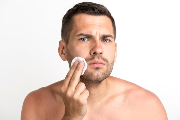 Ernstige jonge mens die zijn gezicht schoonmaakt tegen witte achtergrond