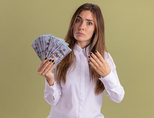 Ernstige jonge, mooie blanke meid houdt geld vast en gebaart vier met vingers geïsoleerd op olijfgroene muur met kopieerruimte