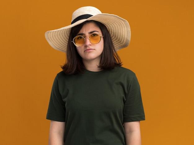 Ernstige jonge, mooie blanke meid in zonnebril en met strandhoed geïsoleerd op een oranje muur met kopieerruimte