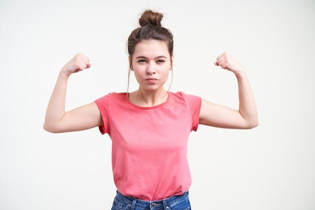 Ernstige jonge mooie bruinharige vrouw met knot kapsel balde vuisten terwijl het demonstreren van macht met opgeheven handen, staande op een witte achtergrond