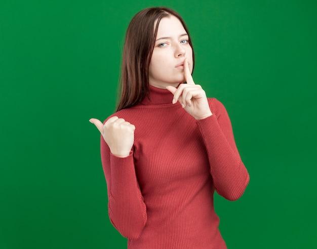 Ernstige jonge mooie vrouw die naar de voorkant kijkt en een stiltegebaar doet wijzend naar de zijkant geïsoleerd op een groene muur met kopieerruimte