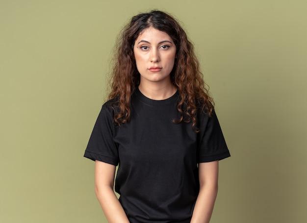 Ernstige jonge mooie vrouw die naar de voorkant kijkt geïsoleerd op een olijfgroene muur met kopieerruimte