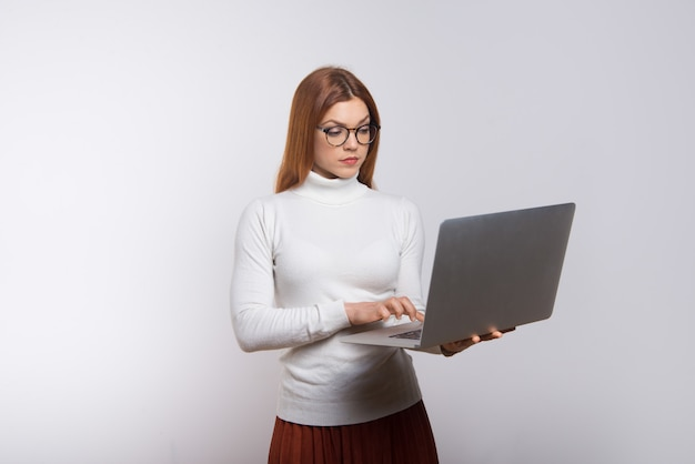 Ernstige jonge onderneemster die laptop met behulp van