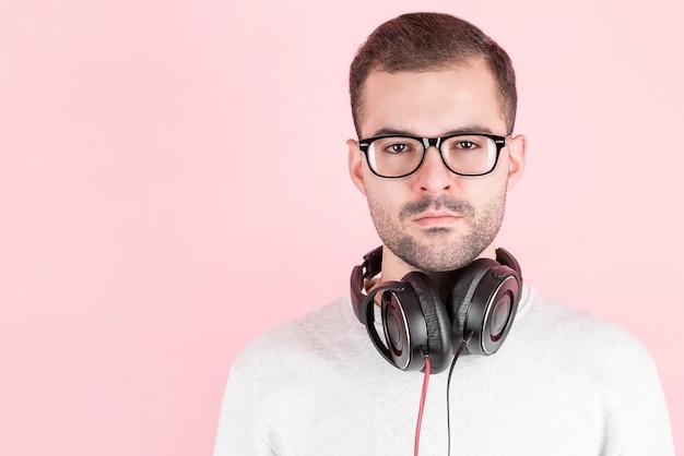 Ernstige jonge schattige jongen luisteren naar muziek in grote witte koptelefoon op roze achtergrond, in wit sweatshirt, wereld dj dag