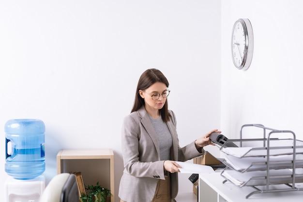 Ernstige jonge secretaris die in functie staat en kopieën van documenten maakt