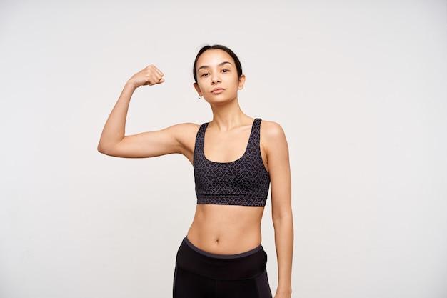 Ernstige jonge slanke bruinharige vrouw zonder make-up hand opsteken terwijl ze haar sterke biceps laat zien en naar voren kijkt met gevouwen lippen, geïsoleerd over witte muur